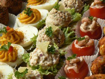 Diverse hapjes op een schaal, zoals gevuld ei en gevulde tomaatjes. Bestel hapjes service bij Catering Service Twente.