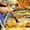 Vrouw pakt aardappelen aan lopend buffet. Besteld bij Catering Service Twente.
