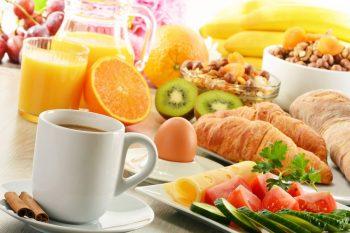 Ontbijttafel met croissants, kop koffie, ei, groentes en verse jus. Besteld bij Catering Service Twente.