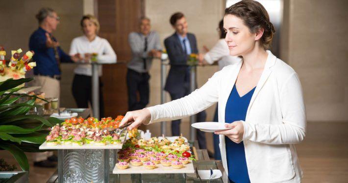 Vrouw pakt hapjes van hapjesschaal. Bestel online hapjes op cateringservicetwente.nl