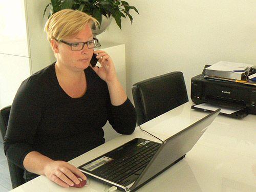 Elvira heeft contact met klant aan tafel voor laptop. Goede service bij Catering Service Twente.